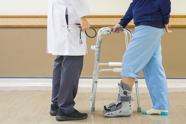 Doctor holding stethoscope in hand, and look patient is required to use walker
