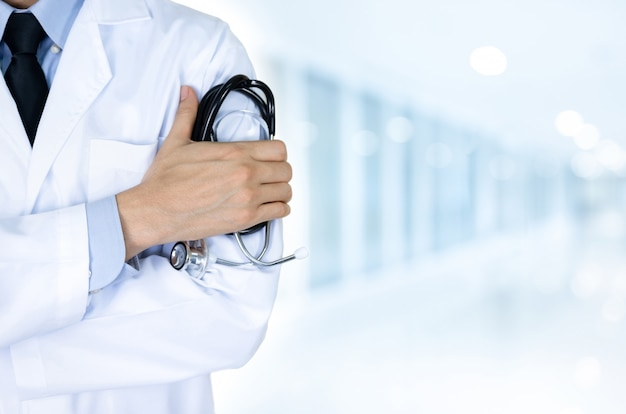 Doctor holding stethoscope at hospital on blur blue background