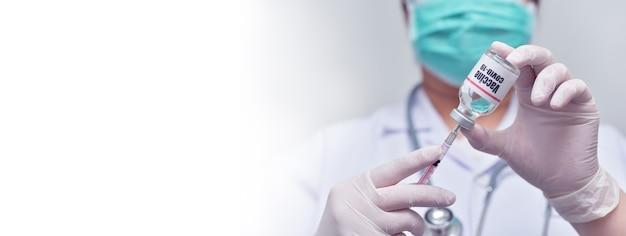 Доктор держит шприц и флакон с вакциной covid-19 - медицина, фармацевтические исследования и концепция здравоохранения