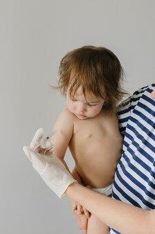 診療所で子供のための注射器皮下ワクチンを保持している医師
