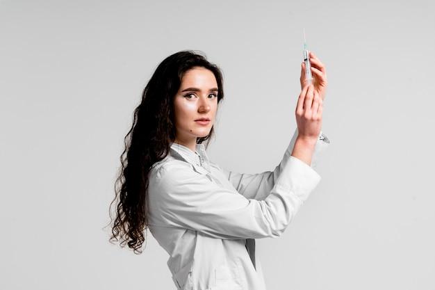 Врач держит шприц с вакциной от коронавируса. вакцинация против covid-19. остановить карантин. привлекательная девушка в медицинских перчатках со шприцем и лекарствами