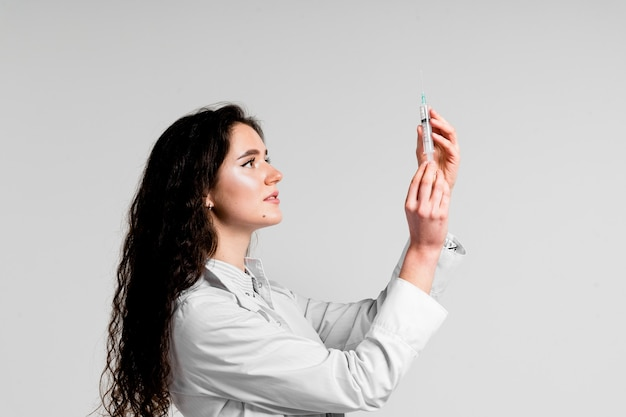 Doctor holding syringe with coronavirus vaccine. covid-19 vaccination. stop quarantine. attractive girl in medical gloves with syringe and medication