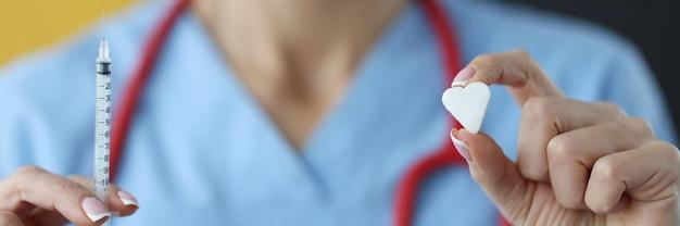 Доктор держит шприц с инсулином и кусок сахара в руке крупным планом