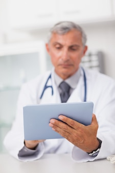 Doctor holding a tablet computer while using it