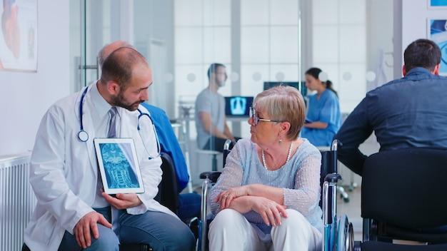 Доктор держит планшетный пк с рентгеновским снимком, объясняя диагноз пожилой женщине-инвалиду в инвалидной коляске. пациент с ограниченными возможностями в зоне ожидания больницы. мужчина в смотровой.