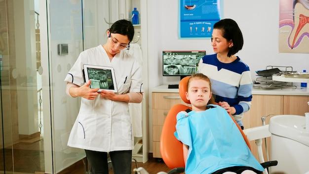 看護師がバックグラウンドでツールを準備している間、医師は女の子の患者の母親にそれを示すx線でタブレットを保持しています。歯科医院で最新のガジェットを使用して歯科x線撮影を提示する歯科医