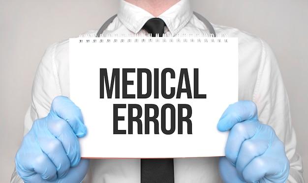 白い紙のメモ帳に医療エラーという言葉を持っている医師