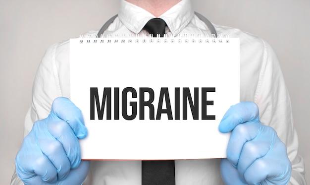 白い紙のメモ帳に「片頭痛」という言葉を持っている医師