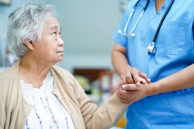 Doctor holding touching hands asian senior or elderly old lady woman patient with love, care.