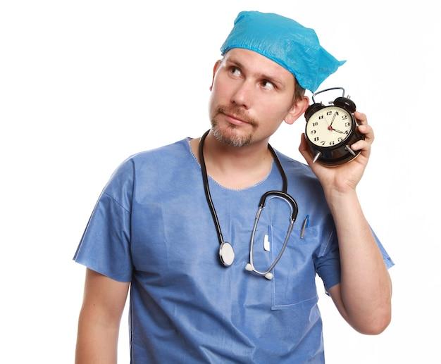 Dottore con in mano un orologio isolato su un muro bianco