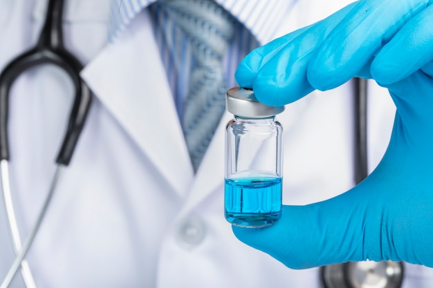 Doctor holding a vial containg blue liquid