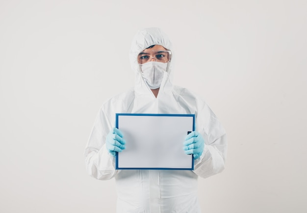 A doctor holding white board in light background in medical gloves and protective suit . coronavirus