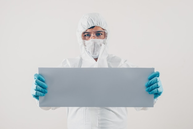 Un medico che tiene cartone bianco in guanti medici e tuta protettiva in sfondo chiaro. spazio per il testo coronavirus
