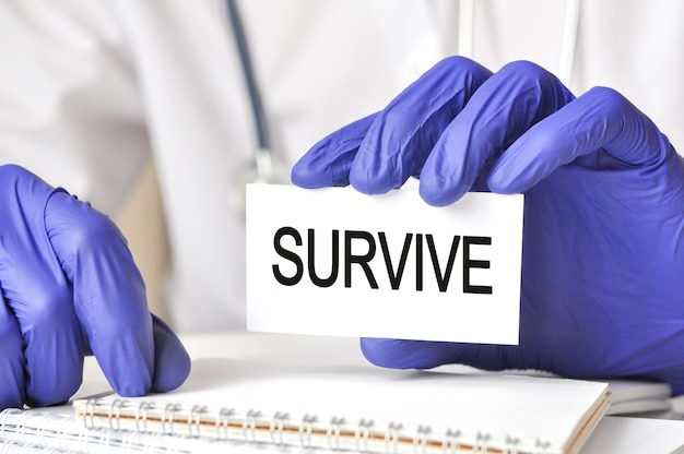 Doctor holding a white paper card with text: survive. healthcare conceptual for hospital, clinic and medical busines.