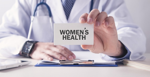 Doctor holding women's health text on card. medical concept