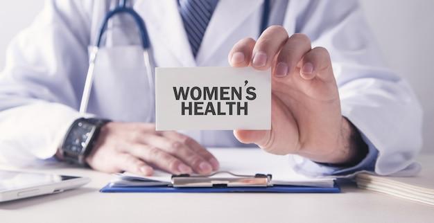 카드에 여성의 건강 텍스트를 들고 의사. 의료 개념