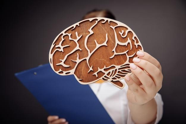 Доктор держит крупный план деревянного мозга. важность концепции ранней диагностики.