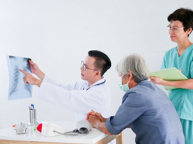 Doctor holding x-ray film in hands present to elderly woman in hospital .health care concept.
