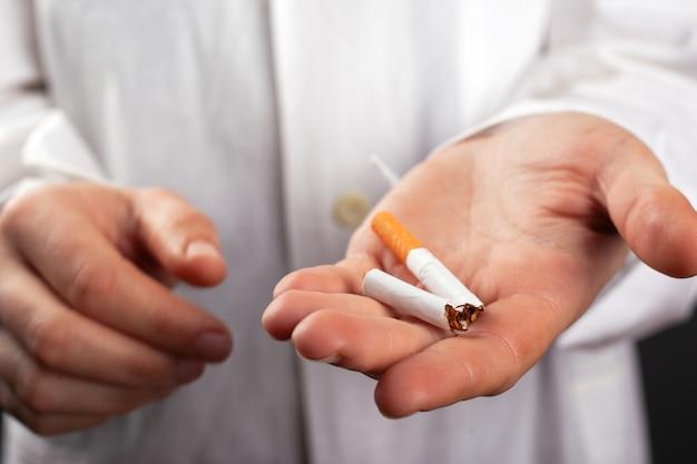 医者は彼の手で壊れたタバコを保持しています。喫煙による害。肺がん疾患はニコチンによる害。