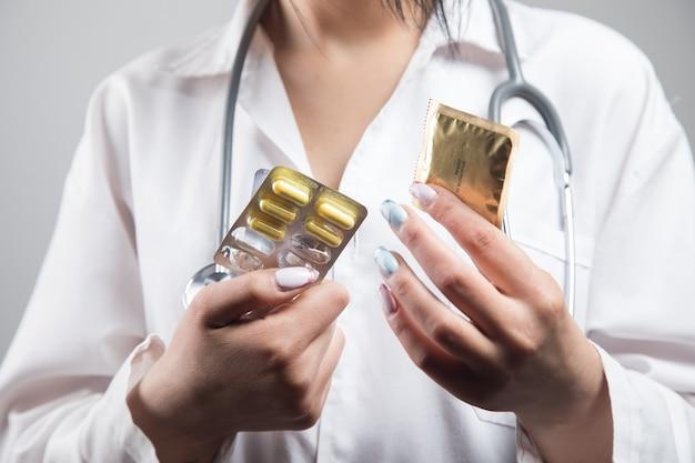 의사는 콘돔과 알약을 보유하고 있습니다. 보호