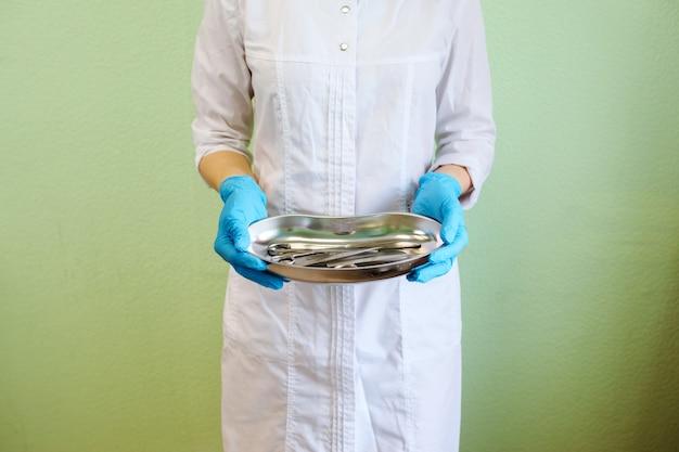 Врач держит поднос в форме почки с маникюрным и педикюрным оборудованием, например, пинцетом и ножницами. медицинский работник одет в белый халат и синие латексные перчатки. зеленая стена фон.
