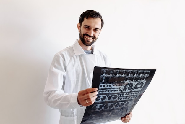 Доктор держит рентген в руках и улыбается на белом