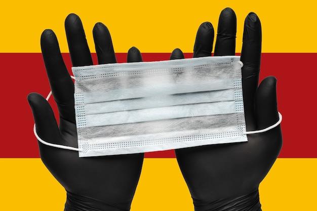 医師は、スペインの背景色の旗に黒い医療用手袋で手にウイルス対策フェイスマスクを保持します。パンデミック保険コロナウイルス、空中感染症、sarsおよびグリッペ。人間の医療用呼吸マスク