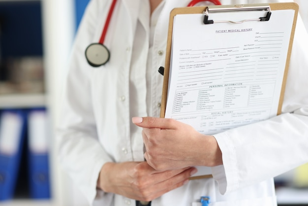 Doctor holds clipboard with the patient medical history