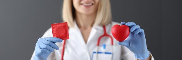 의사는 그의 손 건강 안전과 사랑 개념에 콘돔과 붉은 마음을 보유