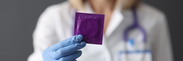 의사는 성교 개념 동안 그의 손 안전에 콘돔을 보유하고 있습니다.