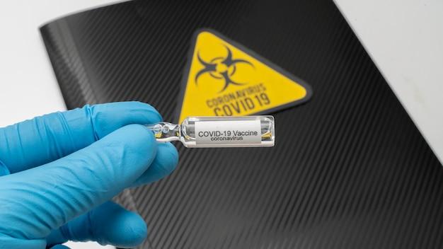 Доктор держит в руке вакцину против коронавируса covid 19. вакцина и для профилактики, иммунизации и лечения от covid-19