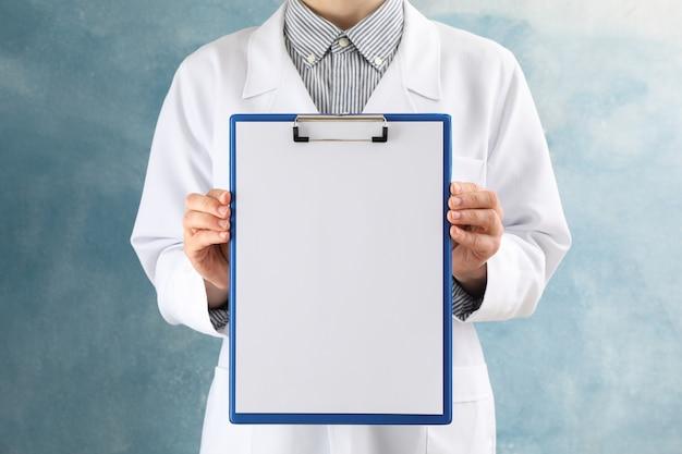 Доктор держит пустой планшет на синем, пространство для текста