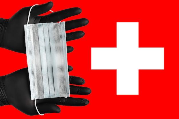 医師はスイスの背景色の旗に黒い医療用手袋でフェイスマスクを手に持っています。コンセプトコロナウイルス検疫、パンデミックの発生、インフルエンザ、空中感染症。人間の呼吸マスク。