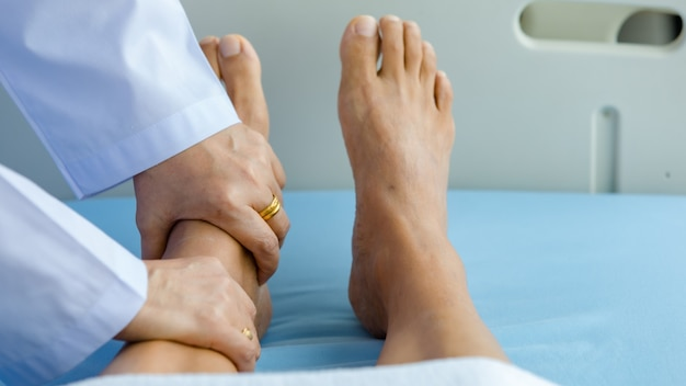 Врач держит пациента ноги на кровати в больнице и проверяет нервную систему для лечения и лечения. понятие синдрома гийена-барре и болезни онемевших рук или побочного эффекта вакцины.