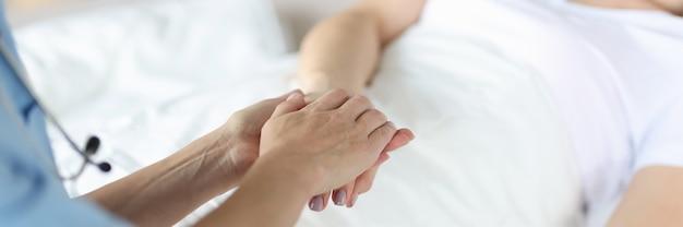 Врач держит лежащего пациента рукой. медицинское обслуживание пациентов в больнице концепции