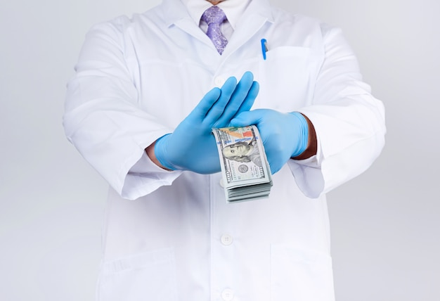 Doctor holds a pack of paper money and refuses to take a bribe