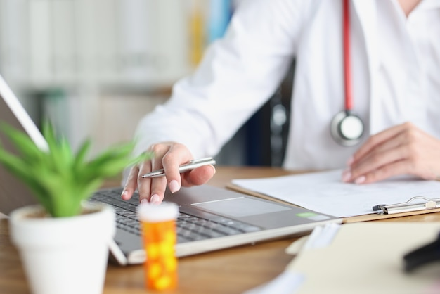 의사가 펜을 보유하고 의료 사무실에서 노트북에서 작동