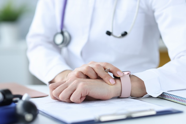 Doctor holds pen and looks at his wristwatch. timely medical examination concept