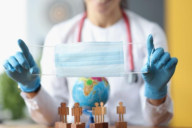 Доктор держит защитную медицинскую маску над деревянными фигурами людей с глобусом