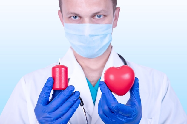 The doctor holds a red heart in his hand and in the other a burning candle.
