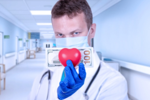 The doctor holds a red heart and a hundred dollar bill.