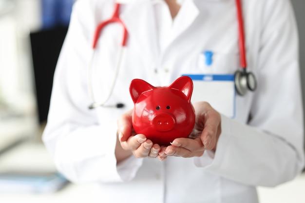 의사는 그의 손에 붉은 돼지 저금통을 보유