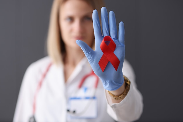 Doctor holds red ribbon in his hand health safety and love concept