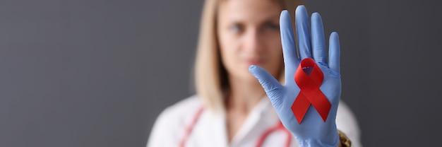 의사는 그의 손 건강 안전과 사랑 개념에 빨간 리본을 보유