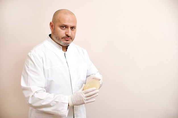 Doctor holds silicone implants for breast augmentation on beige surface