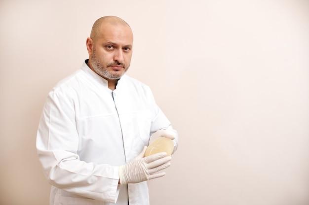 의사가 베이지 색 표면에 유방 확대를위한 실리콘 임플란트를 보유하고 있습니다.