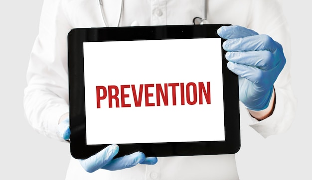 Doctor in holds a tablet with text prevention