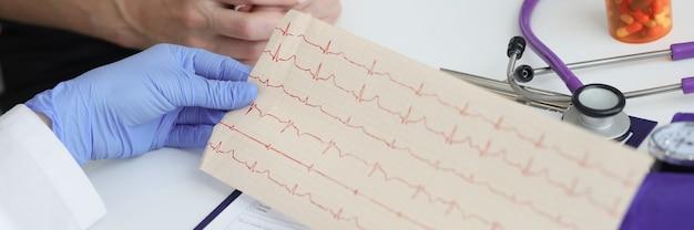 의사는 환자의 심전도 기록을 손에 들고 있습니다.
