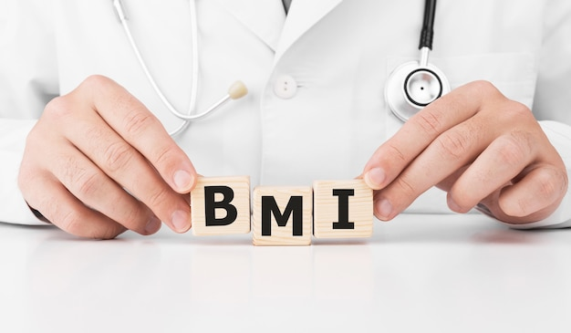 Doctor holds wooden cubes in his hands with text bmi