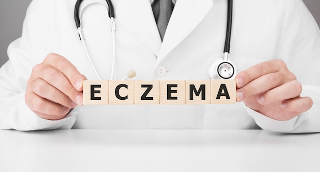 Doctor holds wooden cubes in his hands with text eczema